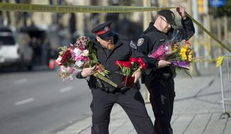 Ottawa Police officers move flowers to an area in front of the National War Memorial near Parliament Hill , where Cpl. Nathan Cirillo, 24, was killed by a gunman in Ottawa on Thursday, Oct. 23, 2014.  Michael Zehaf Bibeau fatally shot  Cirillo on Wednesday, at the National War Memorial before setting his sights on Parliament Hill. Bibeau was killed just feet from where hundreds of MPs were meeting for their weekly caucus meetings.  (AP Photo/The Canadian Press, Justin Tang)
