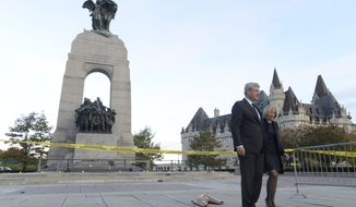 Prime Minister Stephen Harper and his wife Laureen walk away after leaving flowers on the perimeter of the National Memorial in Ottawa Thursday, Oct.  23, 2014. Michael Zehaf Bibeau fatally shot reservist Cpl. Nathan Cirillo at the National War Memorial before setting his sights on Parliament Hill. Bibeau was killed just feet from where hundreds of MPs were meeting for their weekly caucus meetings. (AP Photo/The Canadian Press, Adrian Wyld)