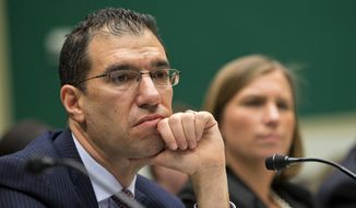 Andrew Slavitt, group executive vice president for Optum/QSSI, left, and Lynn Spellecy, corporate counsel for Equifax Workforce Solutions, listen to questioning during a House Energy and Commerce Committee hearing with contractors that built the federal government's health care websites  in Washington, in this Oct. 24, 2013, file photo. (AP Photo/ Evan Vucci, File)