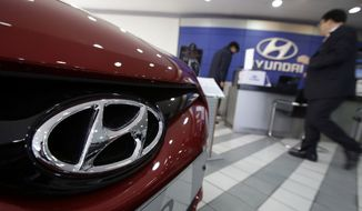 The logo of Hyundai Motor Co. is seen on a car at the automaker's showroom in Seoul, South Korea. Hyundai Motor Co. said Thursday, Oct. 23, 2014, its profit sank nearly 30 percent for the July-September quarter, hurt by a stronger South Korean currency and weak sales growth in its home market.  (AP Photo/Lee Jin-man, File)