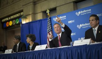 New York City Mayor Bill de Blasio, second from right, speaks during a news conference at Bellevue Hospital to discuss Craig Spencer, a Doctors Without Borders physician who recently returned to the city after treating Ebola patients in West Africa, Thursday, Oct. 23, 2014, in New York. Spencer tested positive for the virus, according to preliminary test results, city officials said Thursday. (AP Photo/John Minchillo)