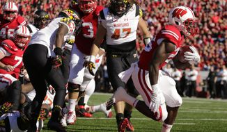 Wisconsin running back Melvin Gordon (25) scores a touchdown against Maryland defensive back Anthony Nixon, left, and Cole Farrand (47) during the first half of an NCAA college football game Saturday, Oct. 25, 2014, in Madison, Wis. (AP Photo/Andy Manis)