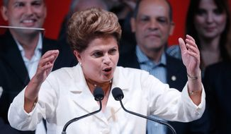 Brazil's President Dilma Rousseff gives her acceptance speech during a press conference in a hotel in Brasilia, Brazil, Sunday, Oct. 26, 2014. Official results showed Sunday that President Rousseff defeated opposition candidate Aecio Neves of the Brazilian Social Democracy Party, and was re-elected Brazil's president. (AP Photo/Eraldo Peres)