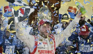 Dale Earnhardt Jr. celebrates after winning the NASCAR Sprint Cup Series auto race at Martinsville Speedway in Martinsville, Va., Sunday, Oct. 26, 2014. (AP Photo/Steve Helber)