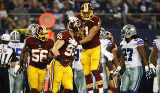 Washington Redskins' Ryan Kerrigan, top, celebrates with Trent Murphy (93) after Murphy recovered a Dallas Cowboys fumble during the first half of an NFL football game, Monday, Oct. 27, 2014, in Arlington, Texas. (AP Photo/Tim Sharp)