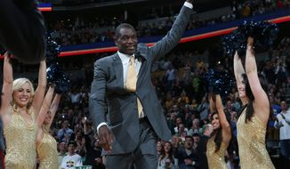 FILE - In this March 17, 2014, file photo, former Denver Nuggets center Dikembe Mutombo waves to crowd as he is introduced during a halftime ceremony in Denver. NBA Commissioner Adam Silver will run the first three miles of the New York City Marathon on Sunday, Nov. 2, 2014,  as part of a 24-person relay of basketball luminaries. Mutombo will cross the finish line for the group, which is promoting the benefits of active lifestyles.  (AP Photo/David Zalubowski, File)