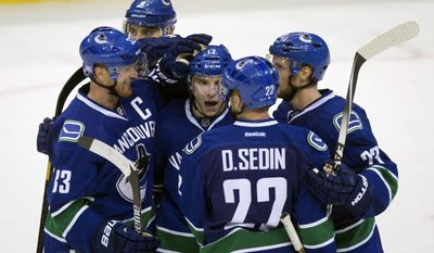 Vancouver Canucks' Henrik Sedin, of Sweden, from left, Chris Tanev, Radim Vrbata, of the Czech Republic, Daniel Sedin, of Sweden, and Alexander Edler, of Sweden, celebrate Vrbata's empty net goal against the Washington Capitals during the third period of an NHL hockey game in Vancouver, British Columbia, on Sunday, Oct. 26, 2014. (AP Photo/The Canadian Press, Darryl Dyck)