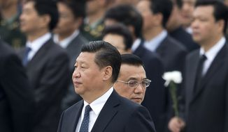In this file photo taken Tuesday, Sept. 30, 2014, Chinese Premier Li Keqiang, right, walks past Chinese President Xi Jinping as they arrive at the Monument to the People's Heroes during a ceremony marking Martyr's Day at Tiananmen Square in Beijing, China. Afghan President Ashraf Ghani Ahmadzai travels to China on Tuesday, Oct. 28, signaling the pivotal role he hopes Beijing will play in Afghanistan's future, not only in the economic reconstruction of his war-ravaged country after U.S. and allied combat troops leave by the end of the year but also in a strategic foreign policy aimed at building peace across a region long riven by mistrust and violence. (AP Photo/Andy Wong, File)