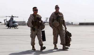 Brigadier Gen. Daniel D. Yoo, left, commanding general, Marine Expeditionary Brigad ; Afghanistan, and Sgt. Maj. Doug Berry Jr., sergeant major, MEB-A, exit a UH-1Y Huey following their landing at Kandahar Airfield in Kandahar province, Afghanistan, Oct. 27, 2014. The Marine Corps ended operations in Helmand province and transferred Camps Bastion and Leatherneck to the Afghan National Army.