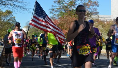 A runner carries the American flag doing the 39th annul Marine Corp Marathon on Suday, October 26, 2004, Khalid Naji-Allah/ Special to the Washington Times