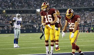 Washington Redskins' Colt McCoy (16) and Roy Helu (29) celebrate after McCoy scored a touchdown on a run during the second half of an NFL football game against the Dallas Cowboys, Monday, Oct. 27, 2014, in Arlington, Texas. Cowboys' George Selvie (99) watches from the rear. (AP Photo/Tim Sharp)