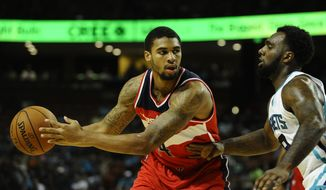 Washington Wizards guard Glen Rice Jr. (14) looks to score as Charlotte Hornets center Bismack Biyombo (8) defends during the first half of a preseason NBA basketball game, Friday, Oct. 10, 2014, in Greenville, S.C. Charlotte won 99-86. (AP Photo/Rainier Ehrhardt)