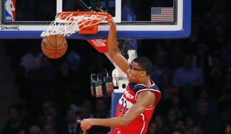 Washington Wizards forward Otto Porter Jr. (22) dunks in front of New York Knicks guard Shane Larkin (0) in the first half of an NBA basketball game at Madison Square Garden in New York, Wednesday, Oct. 22, 2014. (AP Photo/Kathy Willens)