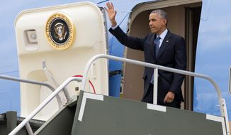 President Barack Obama waves as he steps off Air Force One after arriving at Gen. Mitchell International Airport in Milwaukee, Tuesday, Oct. 28, 2014. Obama is traveling in Milwaukee for a Democratic National Committee fundraiser, and a campaign rally for Wisconsin Democratic gubernatorial candidate Mary Burke. (AP Photo/Evan Vucci)