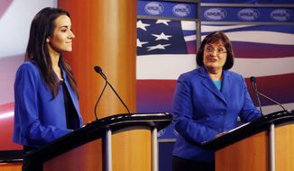 Republican challenger Marilinda Garcia, left, listens as Democratic incumbent Annie Kuster answers a question during a live televised debate for the 2nd District Congressional seat hosted by WMUR, the New Hampshire Union Leader, The New Hampshire Institute of Politics at Saint Anselm College in Manchester, N.H., Tuesday, Oct. 28, 2014. (AP Photo/Jim Cole)