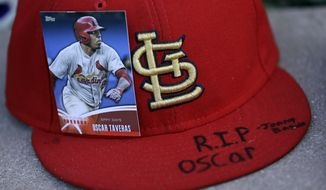 A baseball card showing St. Louis Cardinals' Oscar Taveras is attached to a hat as part of a makeshift memorial outside Busch Stadium Monday, Oct. 27, 2014, in St. Louis. Taveras, the Cardinals' outfielder regarded as one of the majors' top prospects, died Sunday in a car accident in his native Dominican Republic. He was 22. (AP Photo/Jeff Roberson)