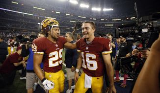 Washington Redskins' Roy Helu (29) and quarterback Colt McCoy (16) celebrate after their NFL football game against the Dallas Cowboys, Monday, Oct. 27, 2014, in Arlington, Texas. Washington won in overtime, 20-17. (AP Photo/Tim Sharp)