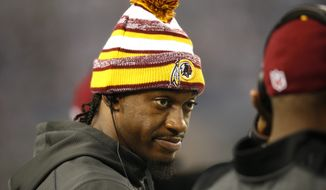 Washington Redskins quarterback Robert Griffin III (10) talks with a teammate on the sideline during an NFL football game against the Dallas Cowboys, Monday, Oct. 27, 2014, in Arlington, Texas. (AP Photo/Tim Sharp)