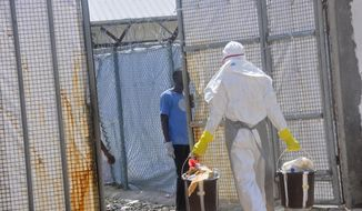 A Ebola health worker removes rubbish including plastic bottles from the Island Clinic Treatment center in Monrovia, Liberia, Wednesday, Oct. 29, 2014. (AP Photo/ Abbas Dulleh)