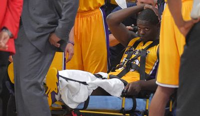 Los Angeles Lakers forward Julius Randle, right, sits on on a stretcher after Randle injured himself on a play during the second half of an NBA basketball game, Tuesday, Oct. 28, 2014, in Los Angeles. (AP Photo/Mark J. Terrill)