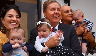 U.S. Sen Lindsey Graham holds 5-month-old Nora Omer, center, along with the triplet's mother Angela Omer , holding Corbett, left, and grandfather Sheldon Waters, holding Oliver, back right, as the senator spoke with supporters and volunteers during a campaign stop at the Spartanburg GOP women's group office, Wednesday, Oct. 29, 2014, in Spartanburg, S.C. (AP Photo/The Spartanburg Herald-Journal, Tim Kimzey)