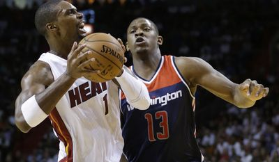 Miami Heat forward Chris Bosh (1) goes up for a shot against Washington Wizards center Kevin Seraphin (13) of France, during the first half of an NBA basketball game, Wednesday, Oct. 29, 2014 in Miami. (AP Photo/Wilfredo Lee)