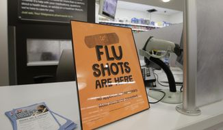 A sign lets customers know they can get a flu shot in a Walgreen store in Indianapolis in this Sept. 16, 2014, file photo. (AP Photo/Darron Cummings) ** FILE **