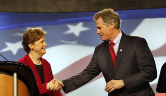 Democrat, U.S. Sen Jeanne Shaheen, left, shakes hands with her Republican opponent, former Massachusetts U.S. Sen. Scott Brown, before a live televised debate for U.S. Senate hosted by WMUR, the New Hampshire Union Leader, and The New Hampshire Institute of Politics at Saint Anselm College, Thursday, Oct. 30, 2014, in Manchester, N.H. (AP Photo/Jim Cole)