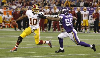 Washington Redskins quarterback Robert Griffin III, left, tries to break a tackle by Minnesota Vikings outside linebacker Marvin Mitchell during the first half of an NFL football game Thursday, Nov. 7, 2013, in Minneapolis. (AP Photo/Ann Heisenfelt)