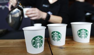 In this March 19, 2014, file photo, Sandy Roberts, Starbucks strategy manager for global coffee engagement, pours samples of coffee for shareholders and other guests, at Starbucks' annual shareholders meeting in Seattle. (AP Photo/Ted S. Warren, File)