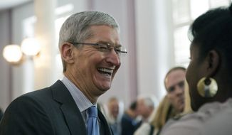 FILE - Apple chief executive and Alabama native Tim Cook laughs with a group before an Alabama Academy of Honor ceremony at the state Capitol in this Oct. 27, 2014 file photo taken in Montgomery, Ala. In an essay written for Bloomberg Businessweek, and published Thursday Oct. 30, 2014  Cook says that while he never denied his sexuality, he never publicly acknowledged it, either.  (AP Photo/Brynn Anderson, File)