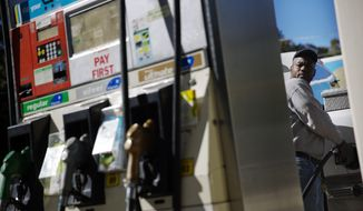 Motorist Jerry Reed watches the pump display while filling up his tank at a gas station, Thursday, Oct. 30, 2014, in Atlanta. (AP Photo/David Goldman) ** FILE **