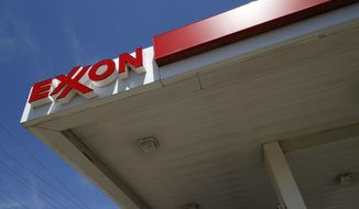 FILE - This July 27, 2011 file photo shows an Exxon sign at an Exxon gas station in Carnegie, Pa. Exxon Mobil reports quarterly financial results on Friday, Oct. 31, 2014.  (AP Photo/Gene J. Puskar, File)
