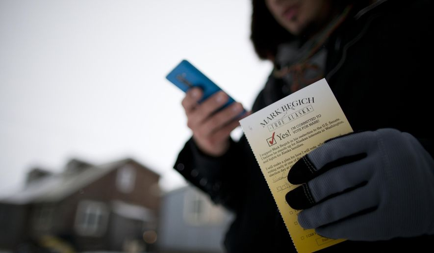 Campaign worker Gabe Tegoseak makes a note on a list of voters he keeps on his phone as he gets a promise card to vote for Sen. Mark Begich from a resident while canvassing in Barrow, Alaska, Thursday, Oct. 9, 2014. (AP Photo/Gregory Bull)
