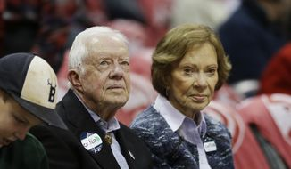 Former U.S. President Jimmy Carter sits with wife Rosalynn while watching an NBA basketball game between the Atlanta Hawks and the Indiana Pacers, Saturday, Nov. 1, 2014, in Atlanta. (AP Photo/David Goldman)
