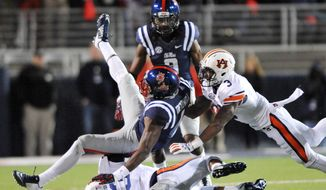 Mississippi wide receiver Laquon Treadwell (1) is tackled by Auburn defensive backs Johnathan Ford (23) and Jonathan Jones (3) during an NCAA college football game in Oxford, Miss,. on Saturday, Nov. 1, 2014. (AP Photo/Oxford Eagle, Bruce Newman)