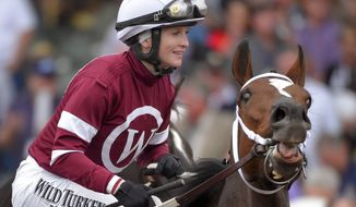 Rosie Napravnik celebrates after riding  Untapable to victory in the Breeders' Cup Distaff horse race at Santa Anita Park Friday, Oct. 31, 2014, in Arcadia, Calif. (AP Photo/Mark J. Terrill)