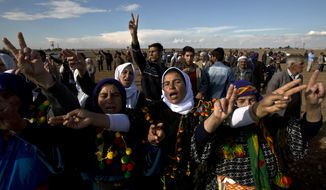 Kurdish women make victory signs while taking part in a solidarity rally with the Syrian city of Kobani in the village of Caykara, Turkey, on the Turkey-Syria border, just across from Kobani, Saturday, Nov. 1, 2014. Tens of thousands of Kurds are rallying in Turkish cities in solidarity with the embattled Syrian city of Kobani, which has been under a brutal siege by the Islamic State group. (AP Photo/Vadim Ghirda) ** FILE **