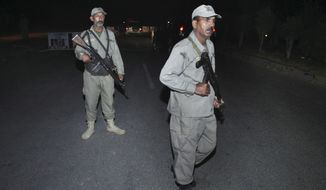 Pakistani paramilitary soldiers stand guard at a cordoned road leading to the site of a bomb explosion in Lahore, Pakistan, Sunday, Nov. 2, 2014. A bomb exploded near a Pakistani paramilitary checkpoint Sunday, killing tens of people near the country's eastern border with India in an attack suspected to be the work of a suicide bomber, police said. (AP Photo/K.M. Chaudary)