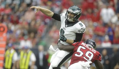 Philadelphia Eagles quarterback Nick Foles (9) is pressured by Houston Texans outside linebacker Whitney Mercilus (59) during the first quarter of an NFL football game, Sunday, Nov. 2, 2014, in Houston. (AP Photo/Patric Schneider)