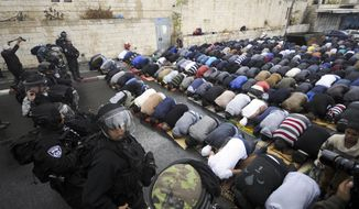 Israeli border police block a road as Palestinians pray in Jerusalem in this Friday, Oct. 31, 2014, file photo. (AP Photo/Mahmoud Illean, File)