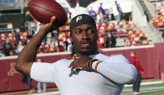 Washington Redskins quarterback Robert Griffin III warms up before an NFL football game against the Minnesota Vikings, Sunday, Nov. 2, 2014, in Minneapolis. (AP Photo/Jim Mone)