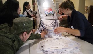 Election officials empty a ballot box during rebel elections at a polling station in the city of Donetsk, eastern Ukraine Sunday, Nov. 2, 2014. The pro-Russian rebels are holding the elections that were dismissed by Ukraine and the West as illegitimate. (AP Photo/Dmitry Lovetsky)