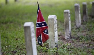A confederate flag is seen at a tombstone on the cemetery at Beauvoir House, Jefferson Davis' historic home, in Biloxi, Miss., Thursday, Aug. 16, 2012. (AP Photo/Gerald Herbert)