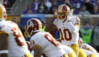 Washington Redskins quarterback Robert Griffin III (10) calls out a play during the second half of an NFL football game against the Minnesota Vikings, Sunday, Nov. 2, 2014, in Minneapolis. (AP Photo/Ann Heisenfelt)