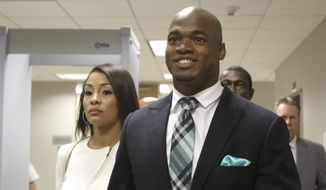 Minnesota Vikings running back Adrian Peterson leaves the courthouse with his wife Ashley Brown Peterson Tuesday, Nov. 4, 2014, in Conroe, Texas. Adrian Peterson avoided jail time on Tuesday in a plea agreement reached with prosecutors to resolve his child abuse case.  (AP Photo/Pat Sullivan)