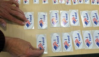 "An election worker lays out ""I Voted"" stickers for voters after they complete their ballots, inside a polling center at the Boulder County Clerk and Recorder's office, in Boulder, Colo., on Election Day, Tuesday Nov. 4, 2014. (AP Photo/Brennan Linsley)"