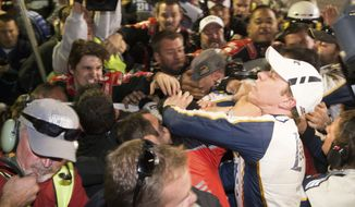 Brad Keselowski, right, is punched during a fight after the NASCAR Sprint Cup Series auto race at Texas Motor Speedway in Fort Worth, Texas, Sunday, Nov. 2, 2014.  The crews of Jeff Gordon and Keselowski fought after the race. (AP Photo/Matthew Bishop)
