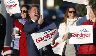 Cory Gardner, center, Republican candidate for the U.S. Senate seat in Colorado, joins supporters in waving placards on the corner of a major intersection in south Denver suburb of Centennial, Colo., early on Tuesday, Nov. 4, 2014. Gardner is facing Democratic incumbent U.S. Sen. Mark Udall in a pitched battle for the seat. (AP Photo/David Zalubowski)