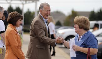 North Carolina Republican Senate candidate, North Carolina House Speaker Thom Tillis, center, and his wife Susan, left, greet a voter at a polling place in Charlotte, N.C., Tuesday, Nov. 4, 2014.  Tillis is running against democratic Sen. Kay Hagan. (AP Photo/Chuck Burton)